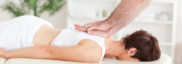 Masseur massaging female customer's back